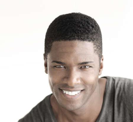 Jonge gelukkig man met grote natuurlijke glimlach tegen witte achtergrond Stockfoto