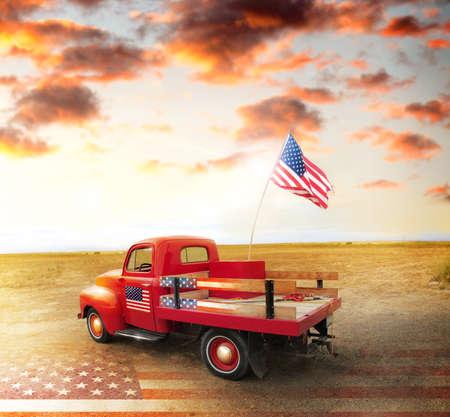 camioneta pick up: Red Vintage camioneta con la bandera americana en el lado ancho campo abierto con espectacular puesta de sol con nubes y la bandera de EE.UU. en el suelo Foto de archivo