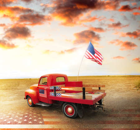 pick: Red vintage pick up truck with American flag in wide open country side with dramatic sunset cloudscape and US flag on ground