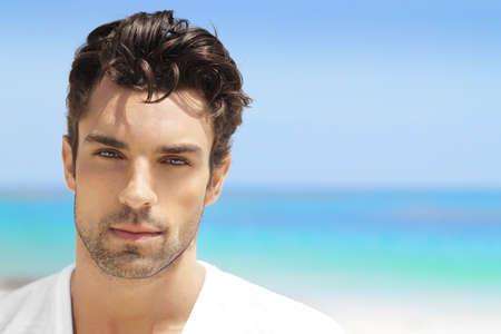 Knappe jonge man in casual witte bovenkant tegen de heldere achtergrond van het strand