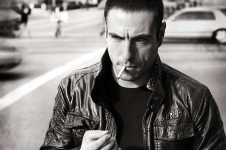 Vintage retro style black and white portrait of a tough sexy guy in leather jacket photo