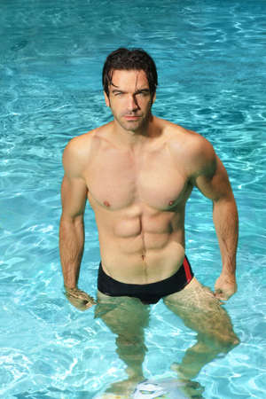 Sexy athletic man standing in bright blue swimming pool