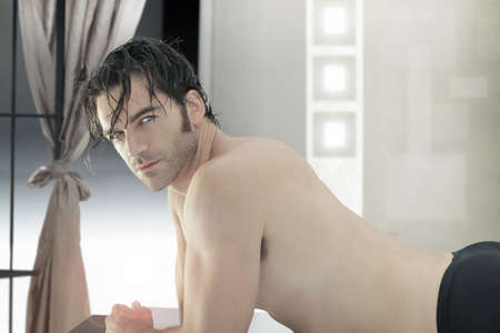 Sexy young man laying down on massage table in modern bright spa environment photo