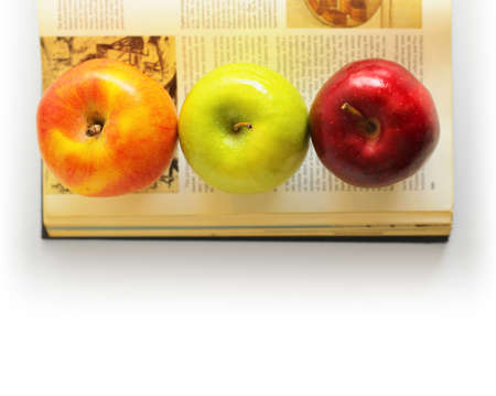 Three distinct apples on top of an old book photo