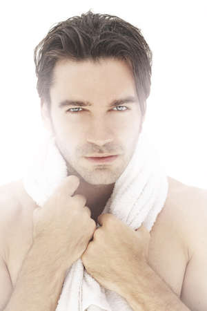 Extremely handsome male model with towel wrapped around neck against white backlit background