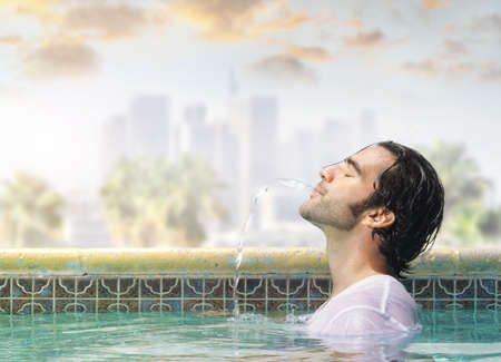 cool guy: Young good looking man in a swimming pool playfully spitting water out of his mouth Stock Photo