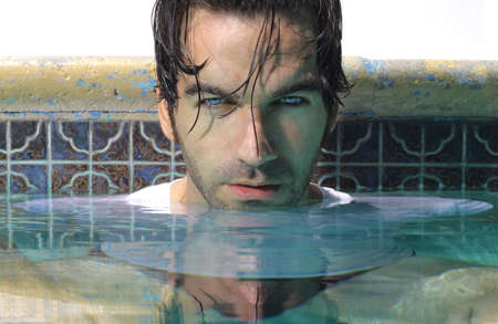 Close face portrait of a handsome sexy man in glamorous swimming pool photo
