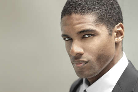 male grooming: Portrait of a good looking handsome young businessman in black suit