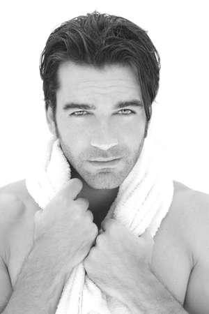 Verse schone close-up portret van een jonge man met een handdoek om zijn nek tegen een witte achtergrond
