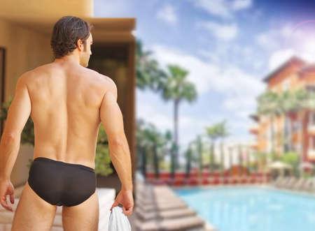 Mooie sexy man met mooie lichaam van achter op glamoureuze toevlucht zwembad Stockfoto