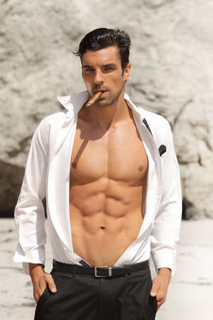 Sexy male model in open shirt exposing great toned muscular body and abs  Stock Photo