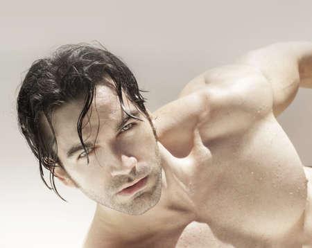 young male model: Sexy joven modelo masculino contra el fondo neutro con expresi�n sensual