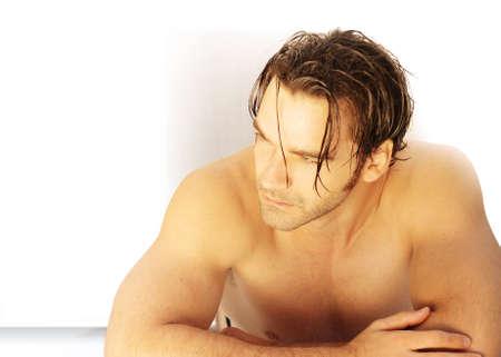 ojos marrones: Guapo el hombre que pone en la mesa con el torso desnudo en la luz cálida tonos de oro con un montón de espacio de la copia