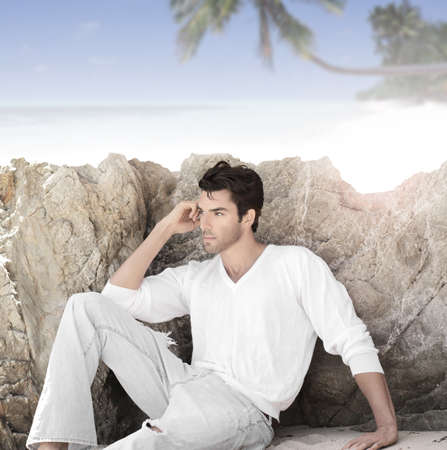 Gorgeous young man in tropical paradise sitting in casual clothes enjoying the surroundings photo