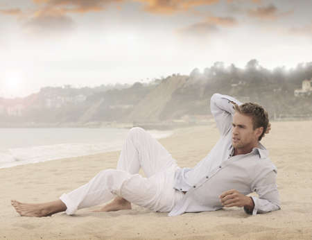 Young relaxed man laying on beach  스톡 콘텐츠