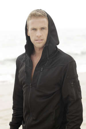 Young handsome man in black hooded active clothing photo