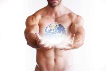 naked man: Very muscular naked man holding a glowing earth globe in his hands with rays of light Stock Photo