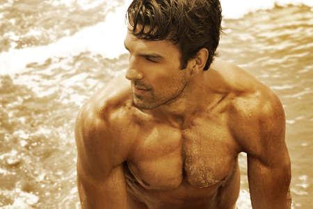 desnudo masculino: Oro retrato de tono fino arte de una hermosa joven musuclar en el océano Foto de archivo