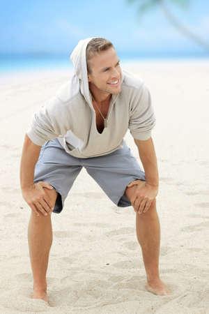 pies masculinos: Chico joven feliz que se divierte en la playa con bonita sonrisa y pies descalzos en la arena Foto de archivo