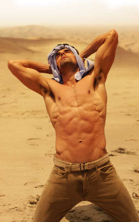 quench: Muscular man without shirt in dry desert looking up Stock Photo