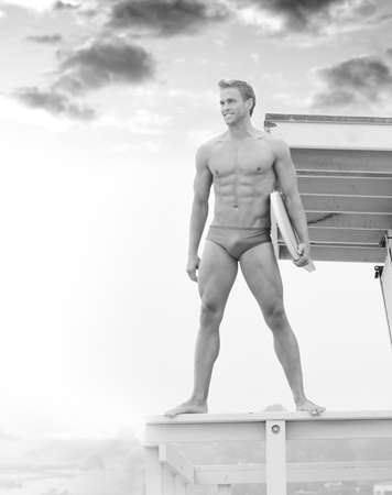 Young fit lifeguard on duty at the beach standing on tower photo