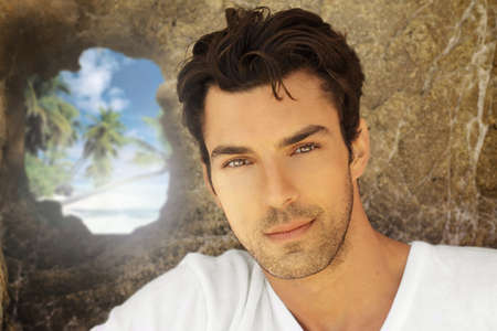 Portrait of a good looking male model against rock formation with hole revealing tropical paradise photo
