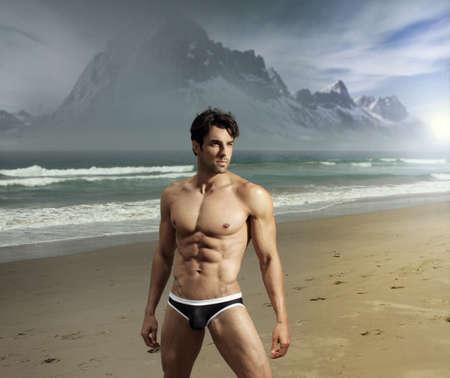 nue plage: Musculaire gars ajustement sexy sur la plage emplacement distant pittoresque avec ses montagnes en arri�re-plan dramatique