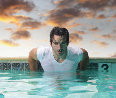 muscle shirt: Sexy young man in luxury swimming pool with beautiful moody sky in background