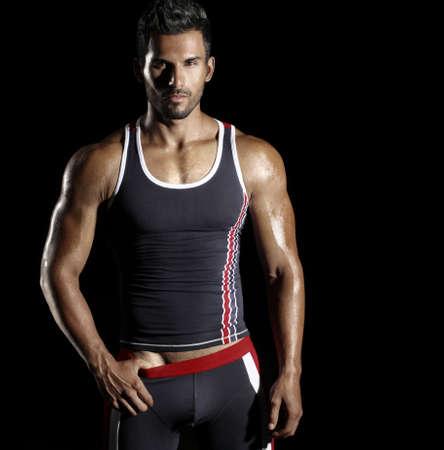 var�n: Muy bien construido sexy modelo masculino en ropa deportiva de moda activo contra el fondo negro con copia espacio