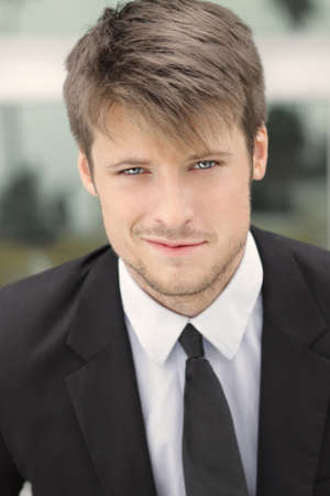 smirk: Happy smart good looking young business man in suit