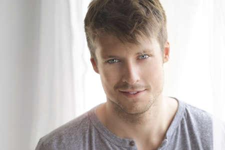 素敵なリラックスした笑顔ときらめく青い目の窓の近くの美しい若い男の親密な肖像画 写真素材 - 14732852