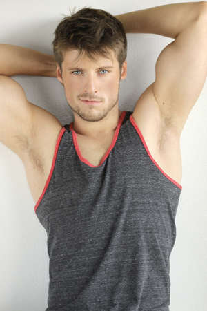 Very good looking young male model with arms up in sexy pose photo