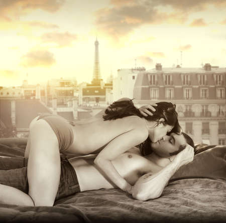 Young sexy couple making passionate love in bed against window overlooking Paris skyline with retro vintage sepia tones Stock Photo - 14732861
