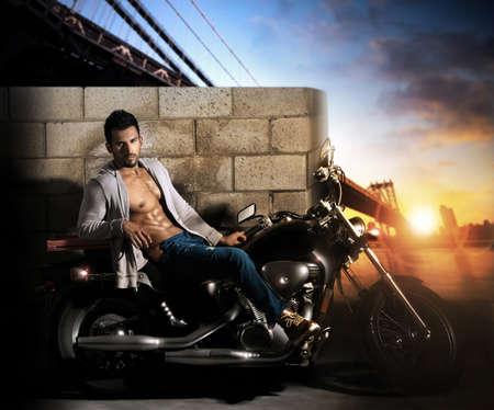 Sexy jonge fit mannelijk model op de motorfiets buiten in de vroege ochtend