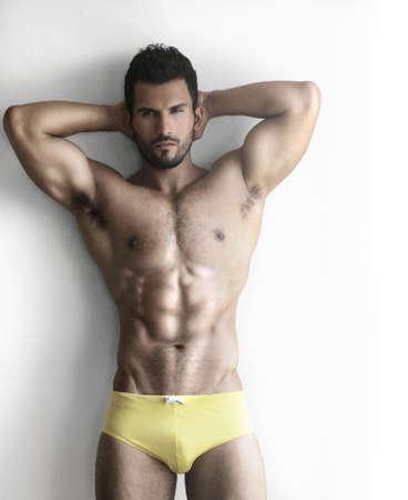 hombre desnudo: Sexy retrato de un modelo muy musculoso torso desnudo masculino en ropa interior contra la pared blanca en pose sensual