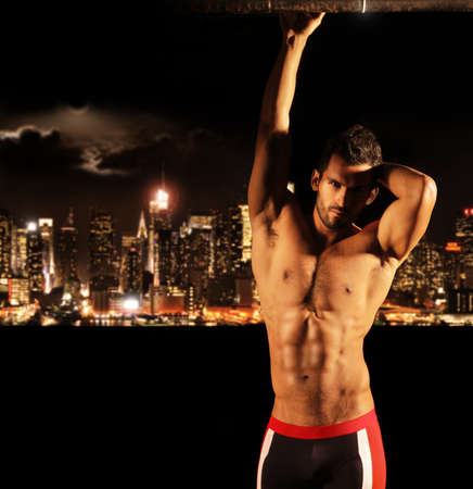 Sexy muscular young shirtless man at night with city lights and skyline in background with copy space Banque d'images