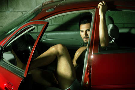 Portrait of a sexy young man sitting in red car Stock Photo - 14840818