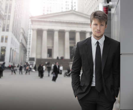 Young attractive businessman outdoors with business district buildings and blurred businesspeople in background