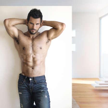 hombre: Retrato de la moda sexy caliente de un modelo masculino en pantalones vaqueros con estilo con el cuerpo musculoso posando en un entorno moderno