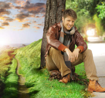 off path: Young stylish happy man in autumn clothing leaning against tree next two path fading off in the distance Stock Photo