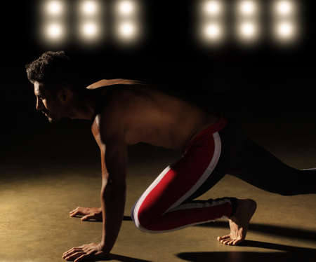 stance: Portrait of an athlete in position to run with stadium lights in background Stock Photo