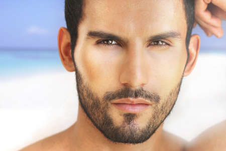 Closeup portrait of a beautiful male model against beach background