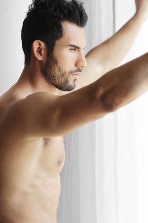 joven desnudo: Retrato de un hombre pensativo hermoso joven desnuda mirando por una ventana pensando