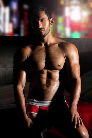 male nude: Buona bodybuilder che cerca sexy posa durante la notte contro le luci della citt� sullo sfondo Archivio Fotografico