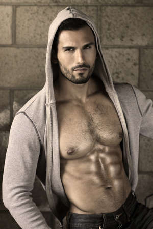 naked man: Young handsome macho man with open jacket revealing muscular chest and abs