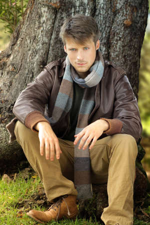 Young handsome man outdoors in fall clothing against tree Banque d'images