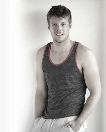 Relaxed portrait of a content young man in tank top with easy smiling expression photo
