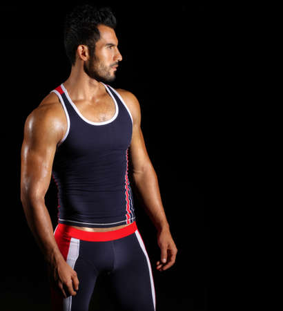 Portrait of a young fit athlete in sportswear against black background with copy space photo