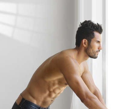 sexy man: Portrait of a thoughtful handsome shirtless young man looking out of a window Stock Photo