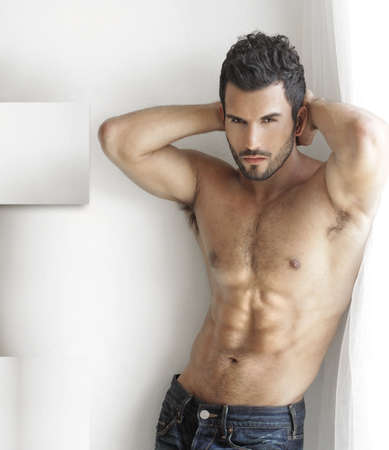 good looking man: Sexy fashion portrait of a hot male model in stylish jeans with muscular body posing in modern interior setting with window light